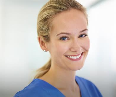 Smiling woman in hospital scrubs